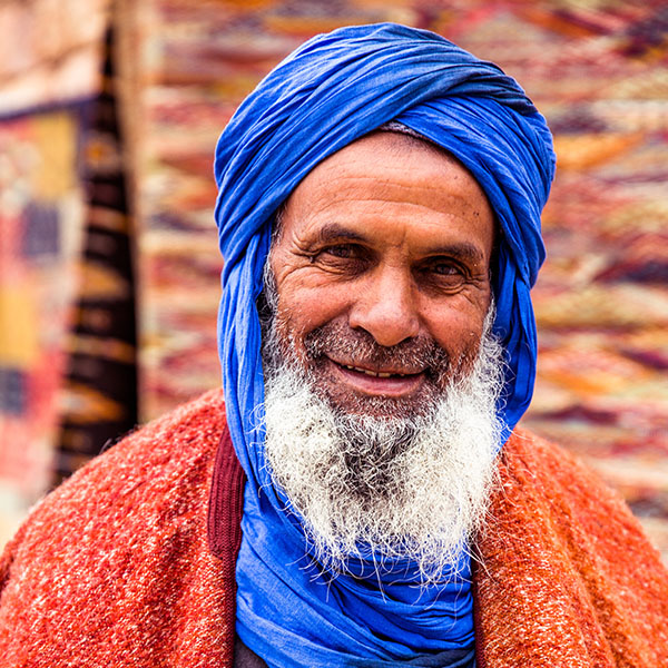 Berber gentleman wearing a Sahara blue scarf, looking to the camera outside of the Berber Boutique displaying traditional rugs.