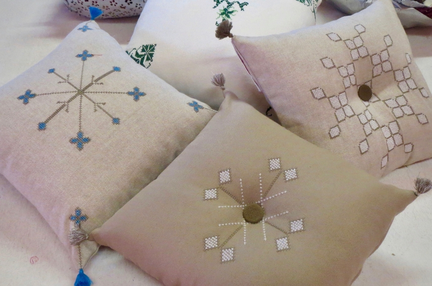 Selection of beige linen square cushions with blue and beige silk embroidery depicting Berber symbols.