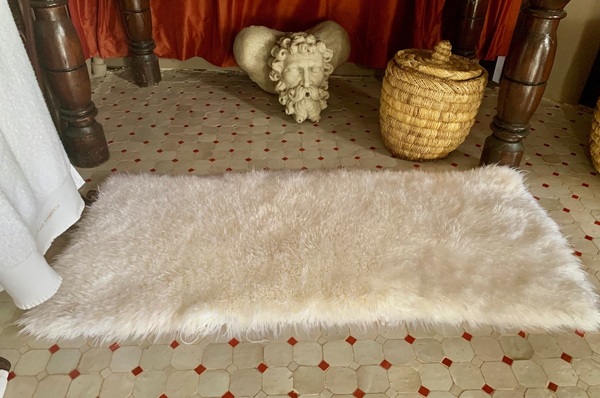 Handmade luxurious deep pile white bath mat on Moroccan tiled floor.