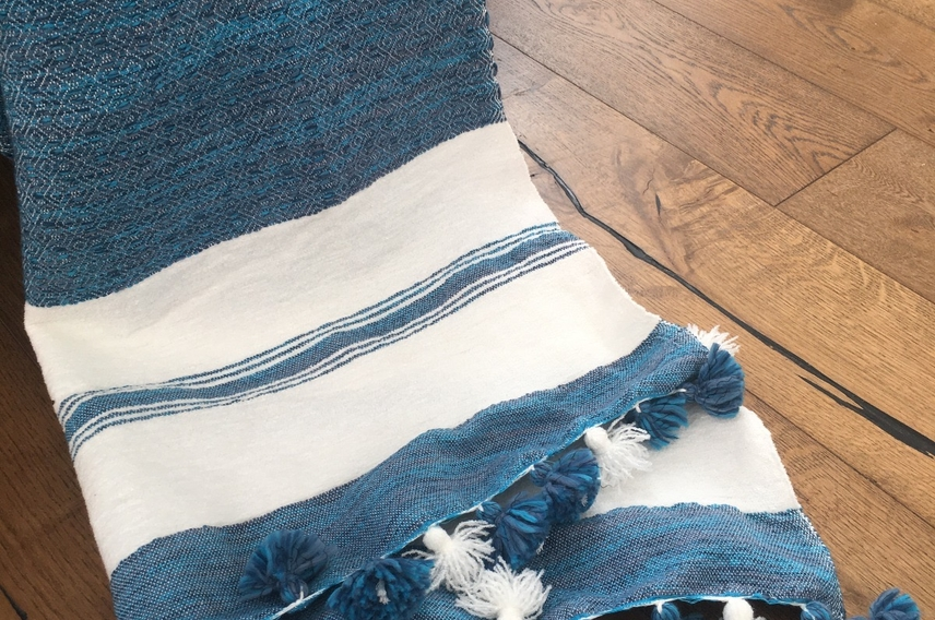 Blue and cream cotton handwoven throw with tassels draped over a chair.