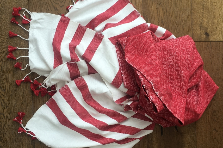 Red and white cotton woven throw with tassels displayed on wooden floor.