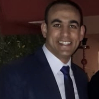 Jamal smiling to the camera, head and shoulders wearing a dark suit and navy silk tie.
