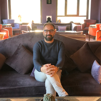 Mohamed sits on a couch with hands folded and smiling in Moroccan lounge at Kasbah Tamadot