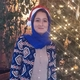 Young woman with bright blue jacket and headscarf standing infront of illuminated tree.